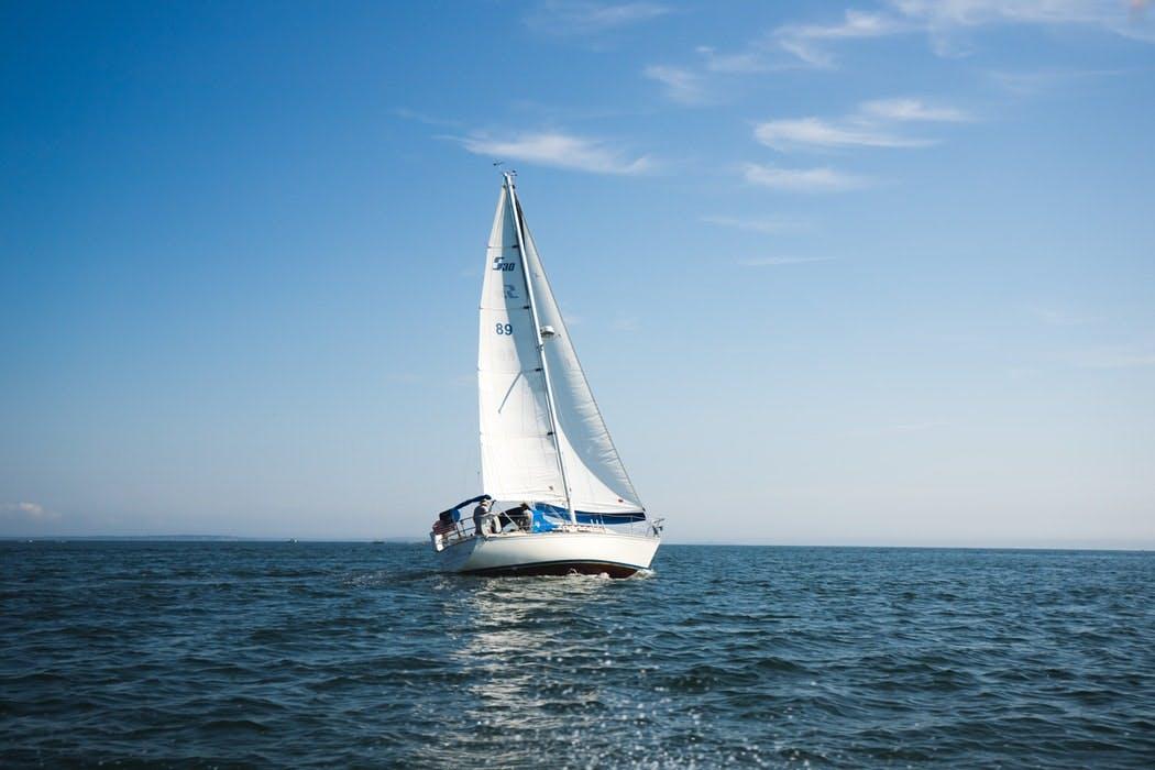 Weißes Segelboot auf offenem Gewässer vor fast wolkenlosem Himmel