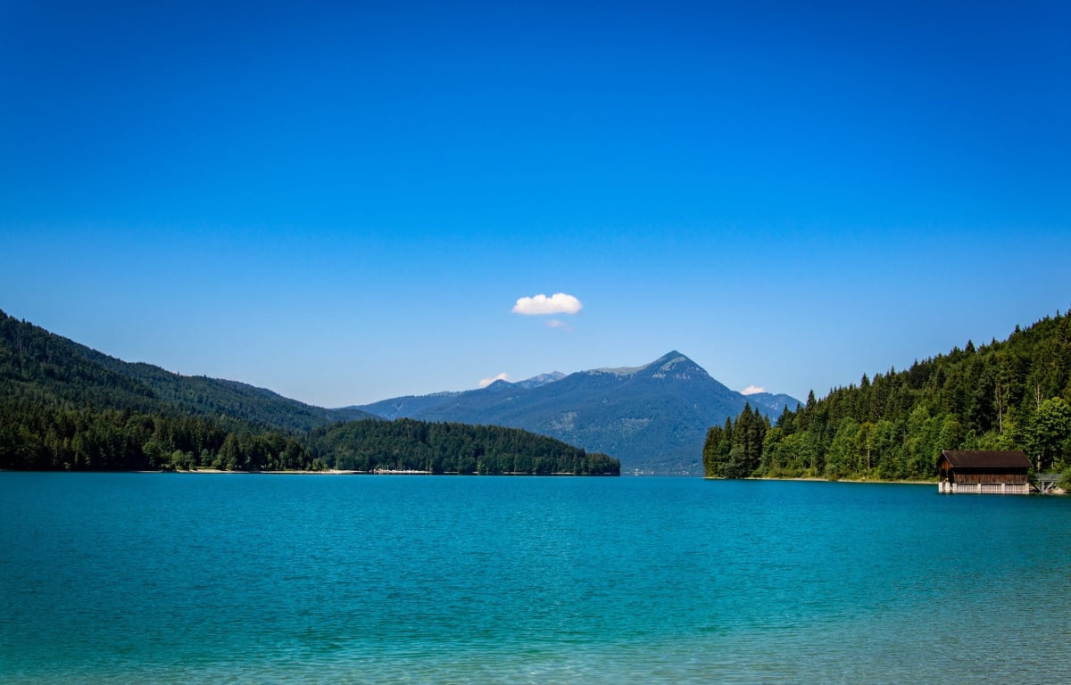 Der Walchensee, ein See in Oberbayern, mit türkis-grünem Wasser und Bergen darum herum.