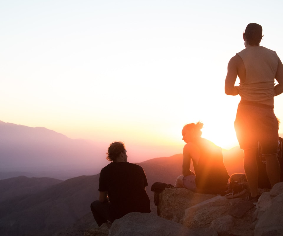 Group of people on a mountain at sunset