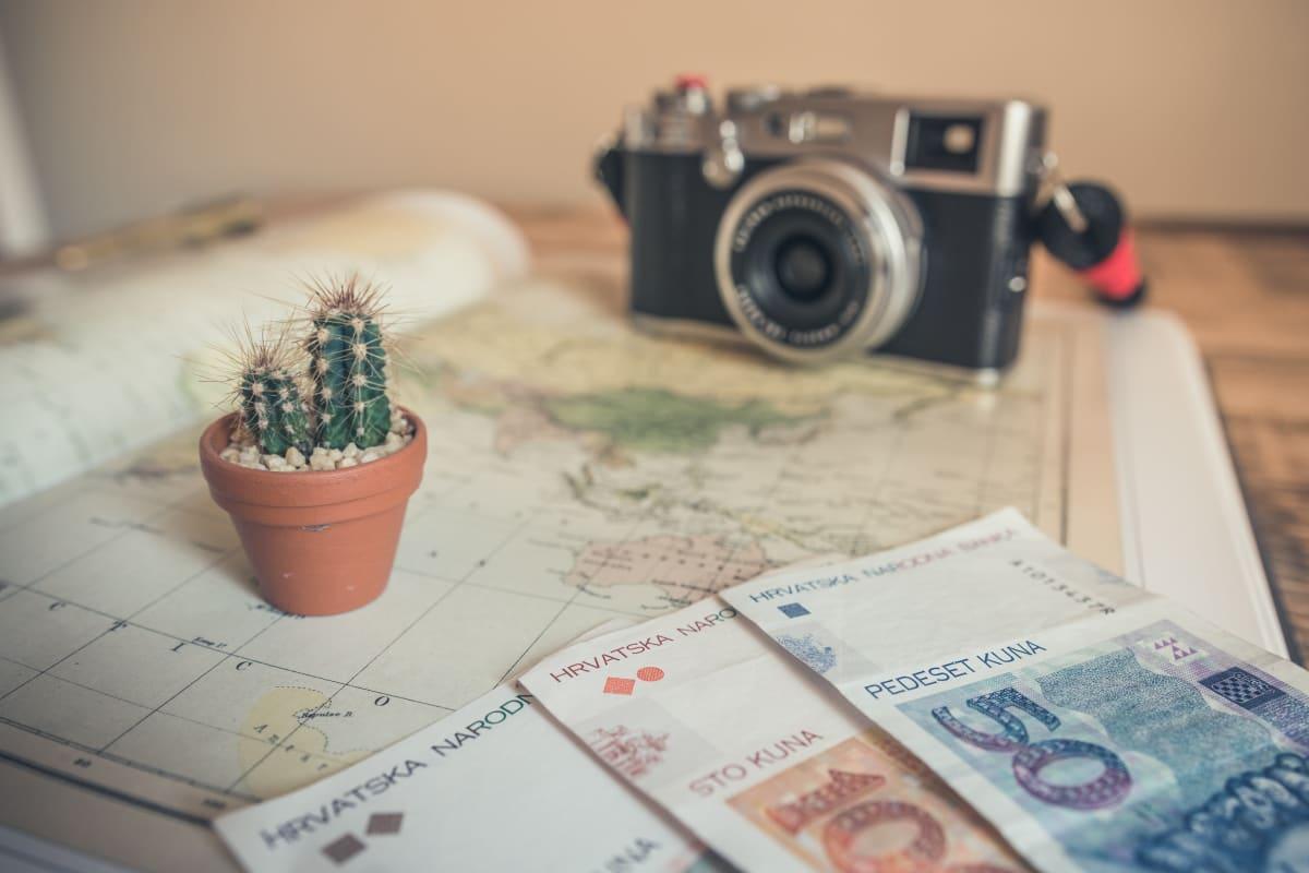 Geldscheine, kleiner Kaktus und altmodische Kamera auf einem Weltatlas ausgebreitet.