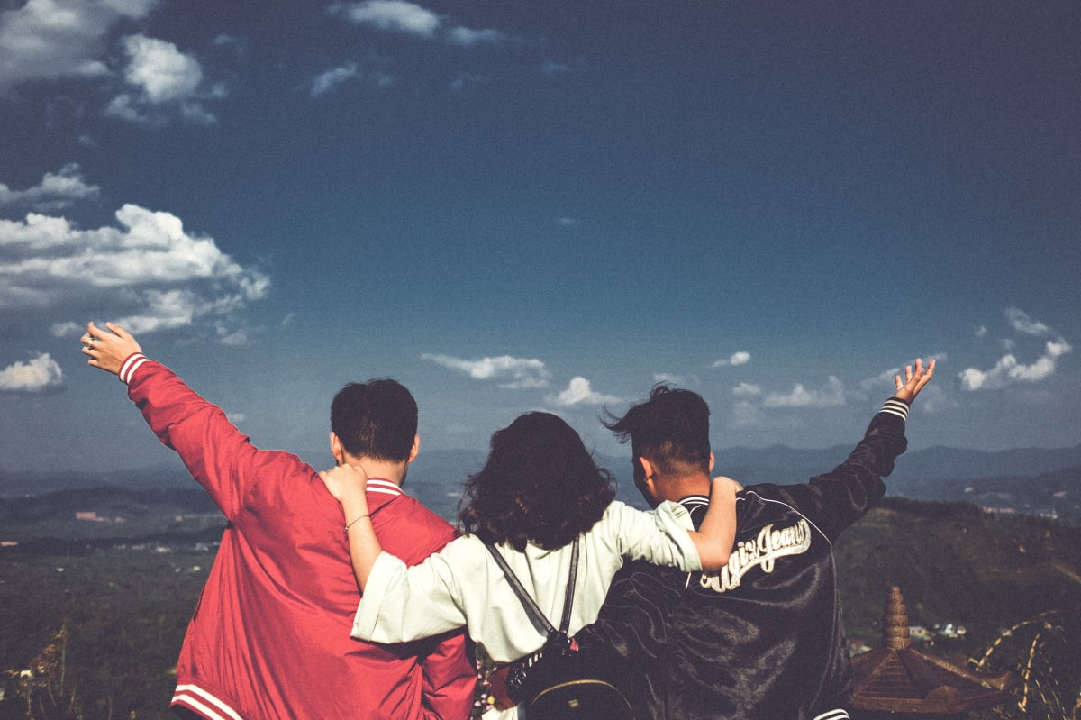three friends standing on top of a mountain looking down, woman has her arms around her two male friends