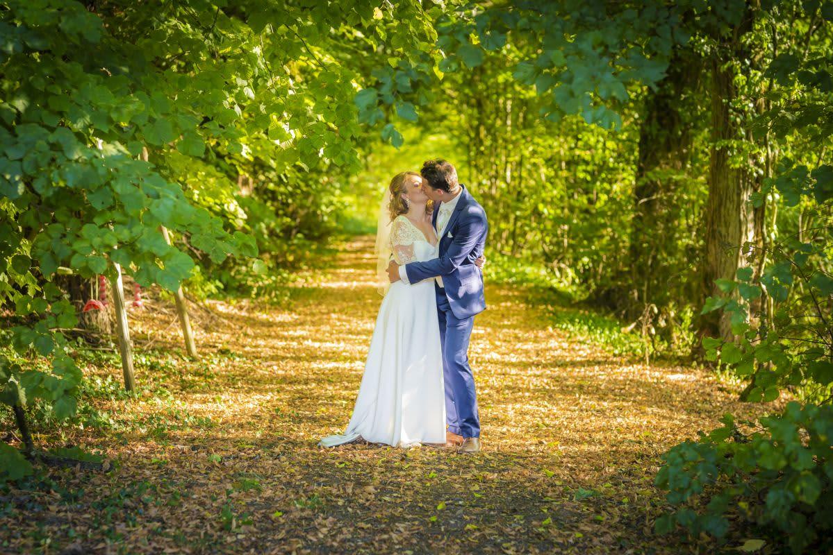 Couple mariés s'embrasse dans un bois