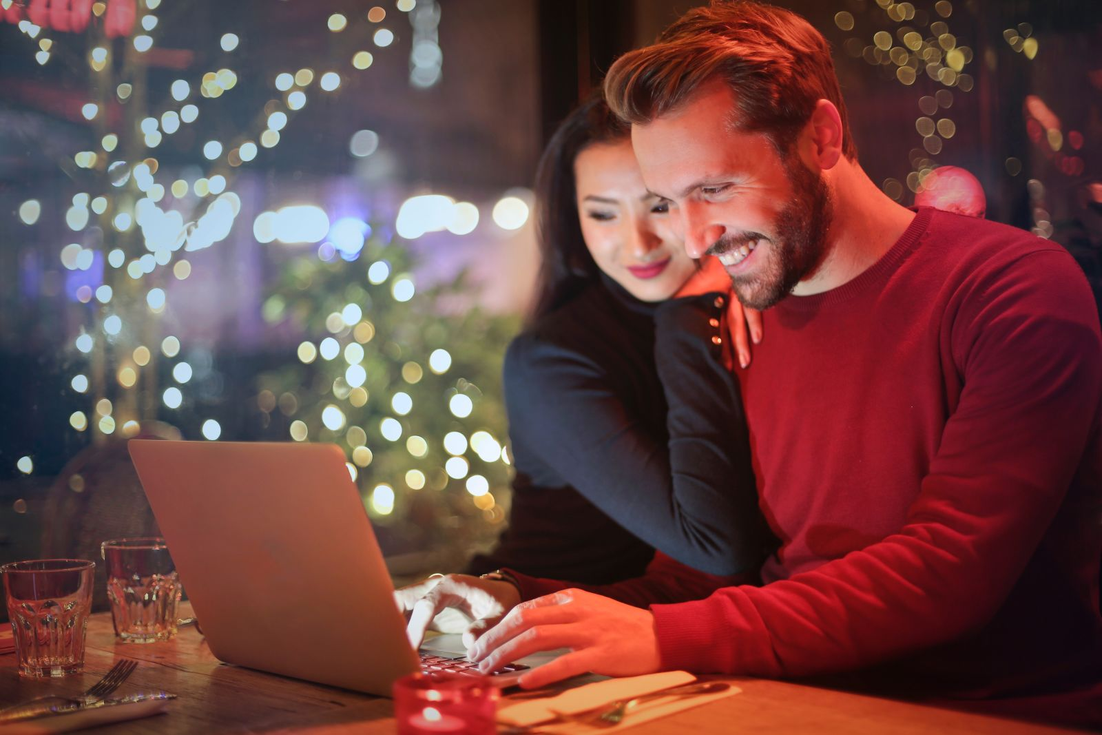 A man and a woman smiling whilst looking at a laptop
