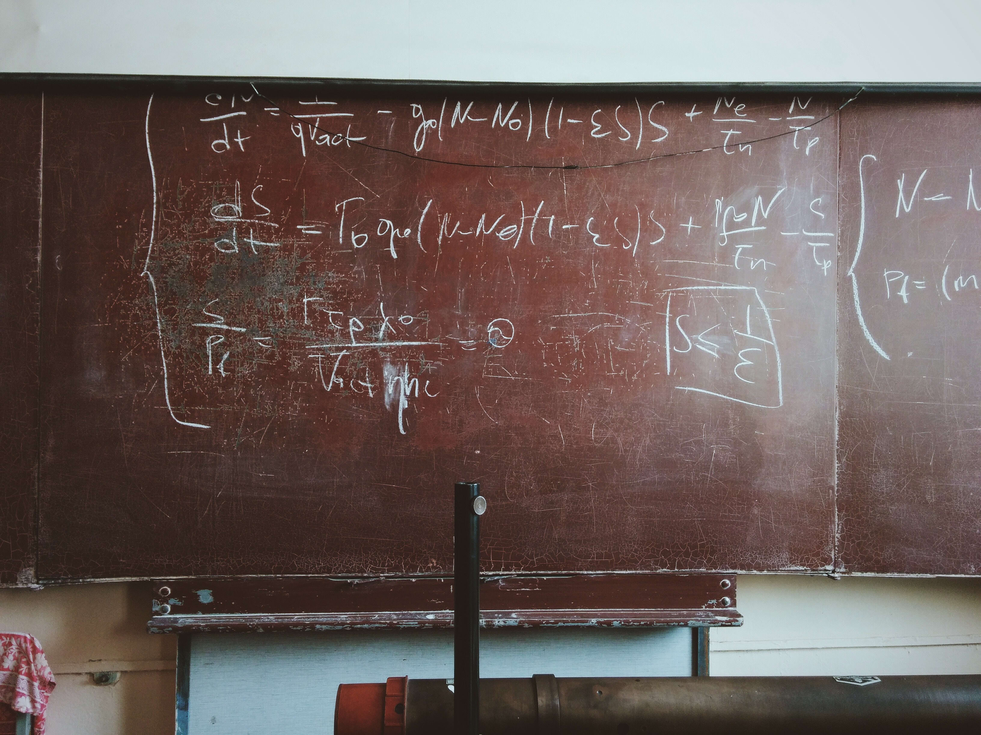 A chalkboard with complicated formulas written on it