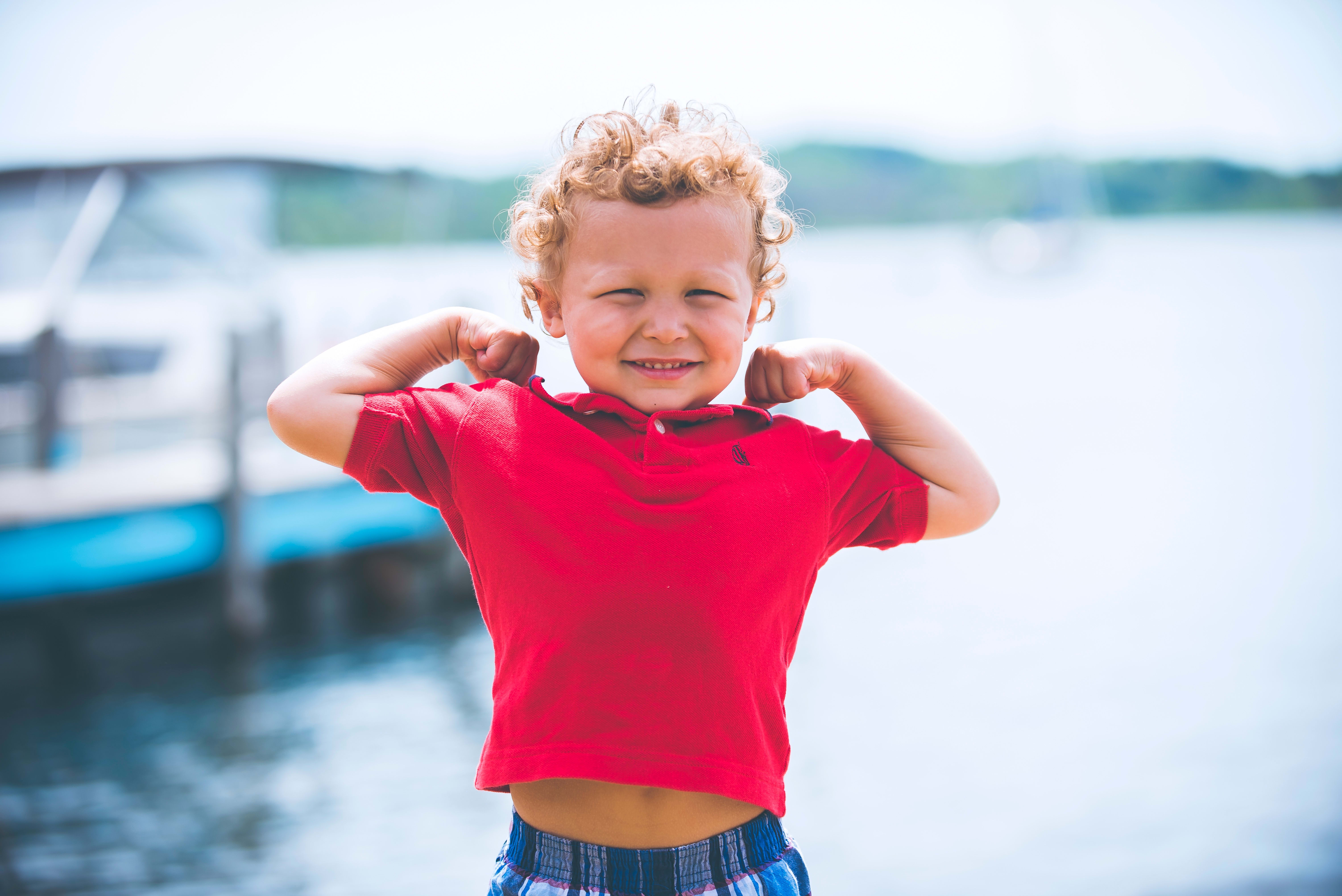 Young boy flexing arms