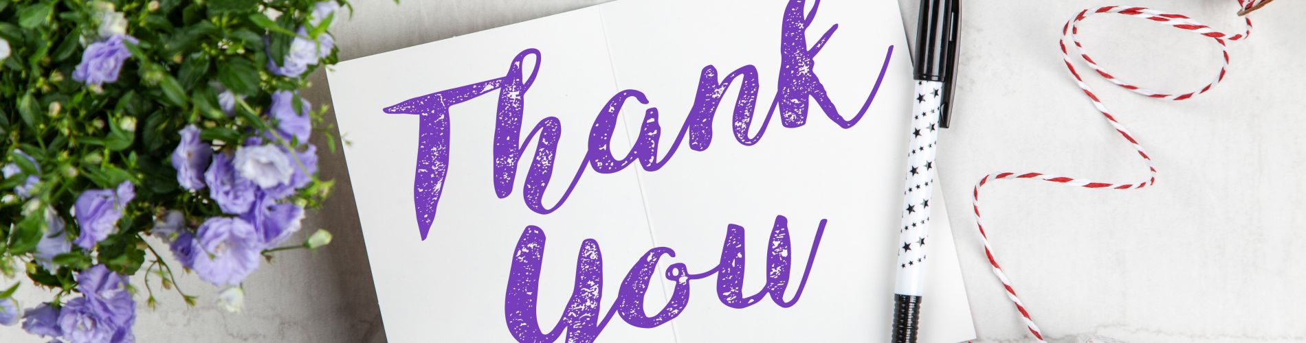 a thank you note with purple flowers