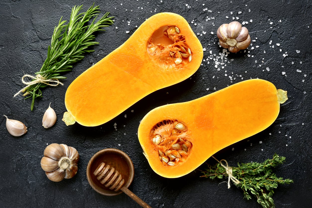 Halves of raw organic butternut squash with spices and ingredients for making