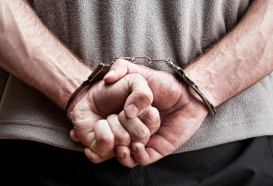 Person with hands in handcuffs behind their back