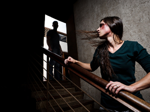Woman running away from man down the stairs