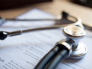 Stethoscope on top of a clipboard with a document attached