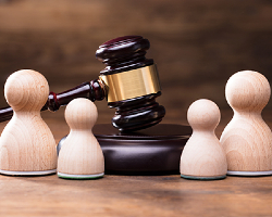 Gavel surrounded by 2 larger chess pieces and 2 smaller pieces