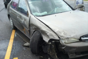 Grey sedan that has been damaged in the front-end