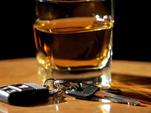 Whiskey glass with car keys nearby