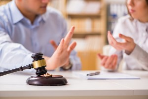 A couple having a discussion near a gavel and two wedding rings