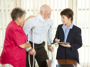 Elderly man on crutches with woman meeting an attorney