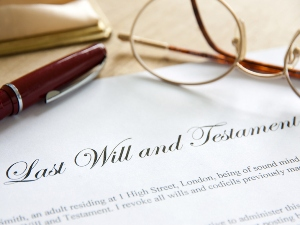 Last will and testament document with glasses and pen