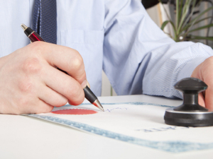 Attorney holding a pen and signing a document