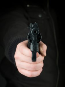 person in all black pointing gun