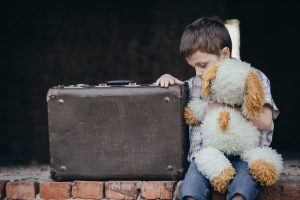 young boy with suitcase and stuffed animal