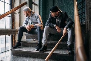 two men sitting on steps one holding baseball bat