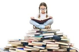 young girl with glassed and pigtails sitting on top of a giant stack of books, looking down at an open book in her lap
