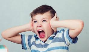 young boy with hands covering his ears and his mouth and eyes wide open appearing to be screaming