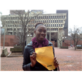 Marie Pascal smiling and holding yellow paper in Massachusetts