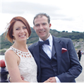 Ciaran Nagle in a suit and Tara Novak in a white dress smiling for a photo
