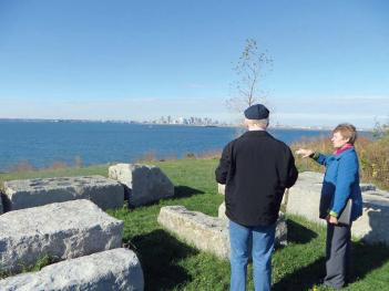 Older man and woman standing by rocks looking out at a body of water