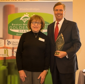 Tall man in suit holding an award smiling for picture with a woman