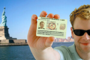 """Man in sun glasses holding a card with his picture that says """"permeant resident card"""" in front of the Statue of Liberty"""