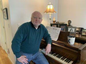 John Foley sitting at piano in his home