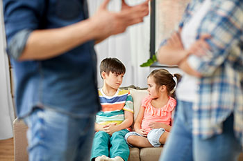 Two adults talking in the forground while child look scared on the couch