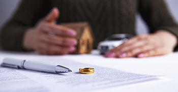 Person gaurding their home and car with divorce papers and a ring in front of them