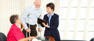 Elderly man on crutches with woman touching his arm both speaking to woman in suit with a clipboard