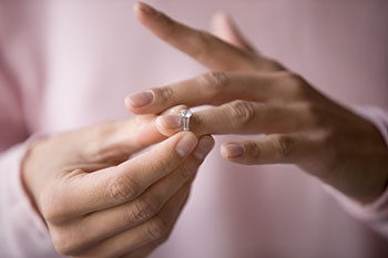 Woman removing diamond ring from her finger