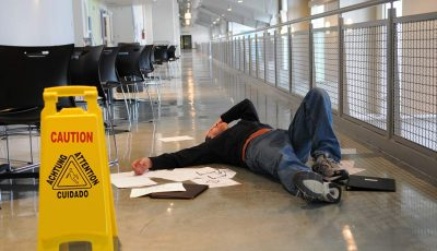 Man lying on floor next to a caution sign with papers scattered around him