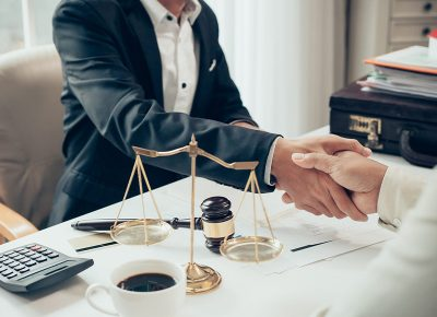 Man in suit shaking hands with person across a table with scales of justice, gavel, a calculator, and a cup of coffee on top