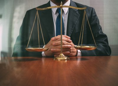 Man in suit sitting at table with scales of justice on the table