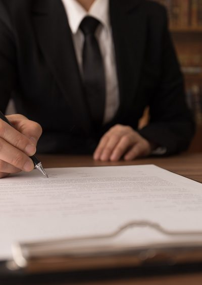 Man in suit signing document