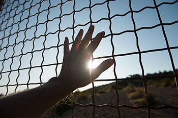 Hand touching the chain link fence