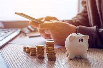 Person working on finances next to piggy bank and coins