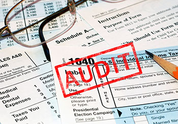 Tax forms with an audit stamp over them