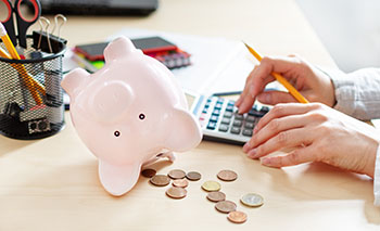 Piggy bank on its side with money coming out of it