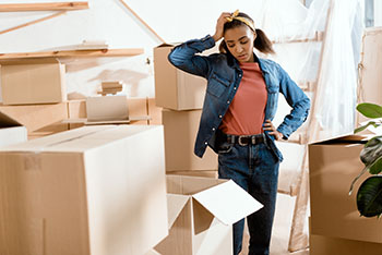 Woman stressed surrounded by moving boxes
