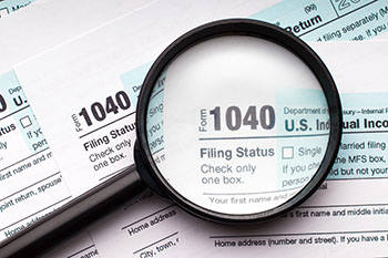 1040 Tax documents with a magnifying glass over them