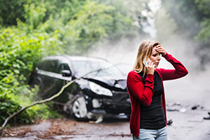 Distressed woman on the phone with a crashed car in the background