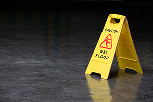 Wet floor sign on a dark grey surface