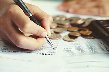A hand is holding a pen over a 1040 document next to a pile of coins