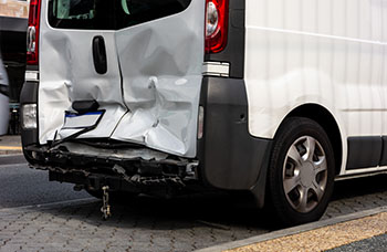 Rear end of a van smashed in